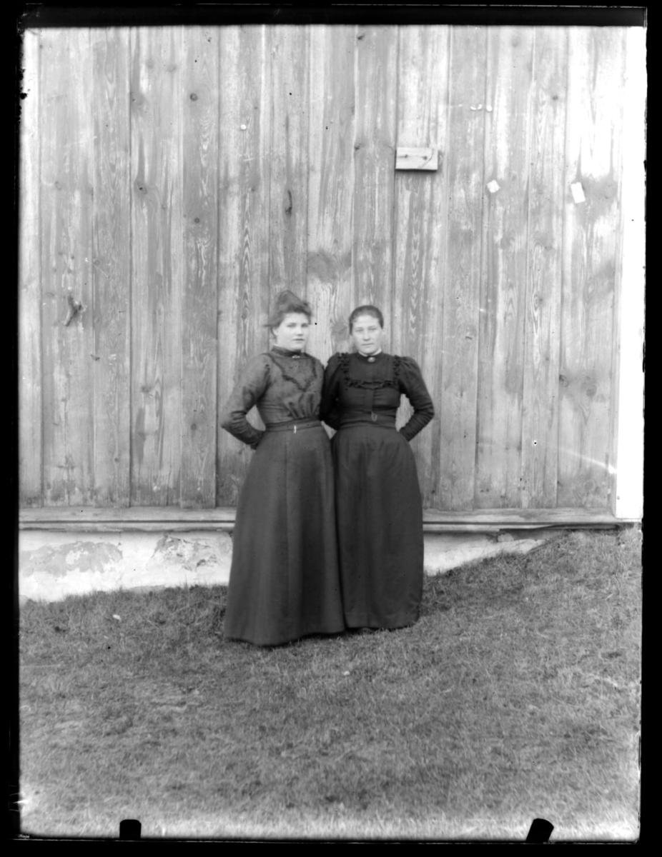 To ukjente kvinner stående mot en husvegg