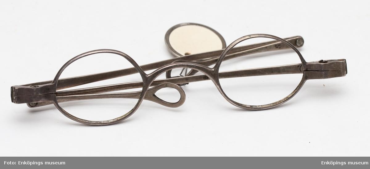 Ett par glasögon med hopfällbara skalmar av silver. Skalmarna slutar i en ögla. Saknar glas. Enkelt, något svängt nässtycke. Troligen tillverkade under 1800-talet.