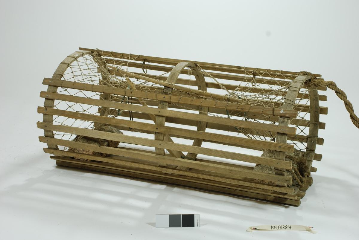 Sylindrisk, rund lektetene med inngang i kortsidene. Intet fangstkammer. Furulekter med eketremeier nederst. Gjorder i ek.  Hjemmespunnet garnbus, kokostau binder 2 tilhuggede stener som vekter.  Agnspyd/matspett) av tre. Gammel lukkepatent med garn og håndspikket pinne.  4 væler (inkl. glasskuler) med Tisler-familiens farger, langt gresstau. 4 væler, trolig fordi man brukte denne på dypere vann. 2 væler i tre, blå og hvite i fargen, avlange. Den ene har spiss ende og avrundede kanter.  1 stk. tilnærmet rektangulær væle i kork.  1 stk glassvæle. Nyere garn i syntetisk fiber rundt glasskule.  Lengste trevæle: 66x8. Korteste trevæle: 43x7. Korkvæle: 17,5x12. Omkrets glasskule: 42