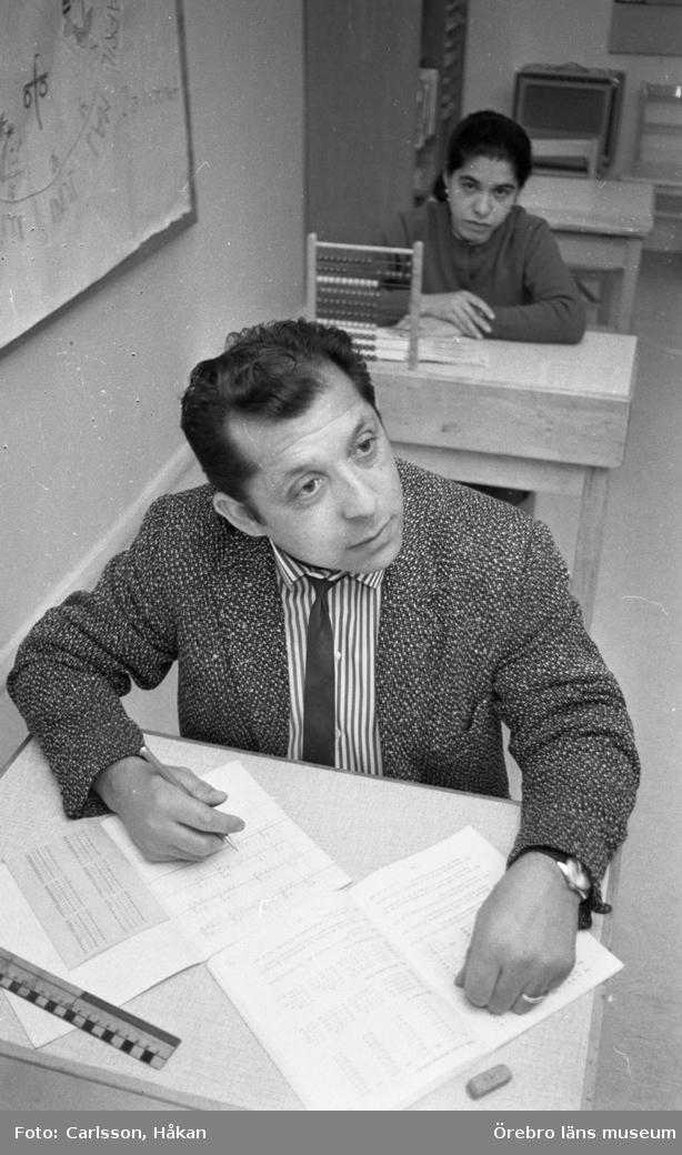 Zigenarskola 4 december 1969En man och en kvinna som är romer sitter i varsin skolbänk. De går en utbildning. Mannen är klädd i en ljus kavaj, randig skjorta och svart slips. På kvinnans skolbänk står en kulram.