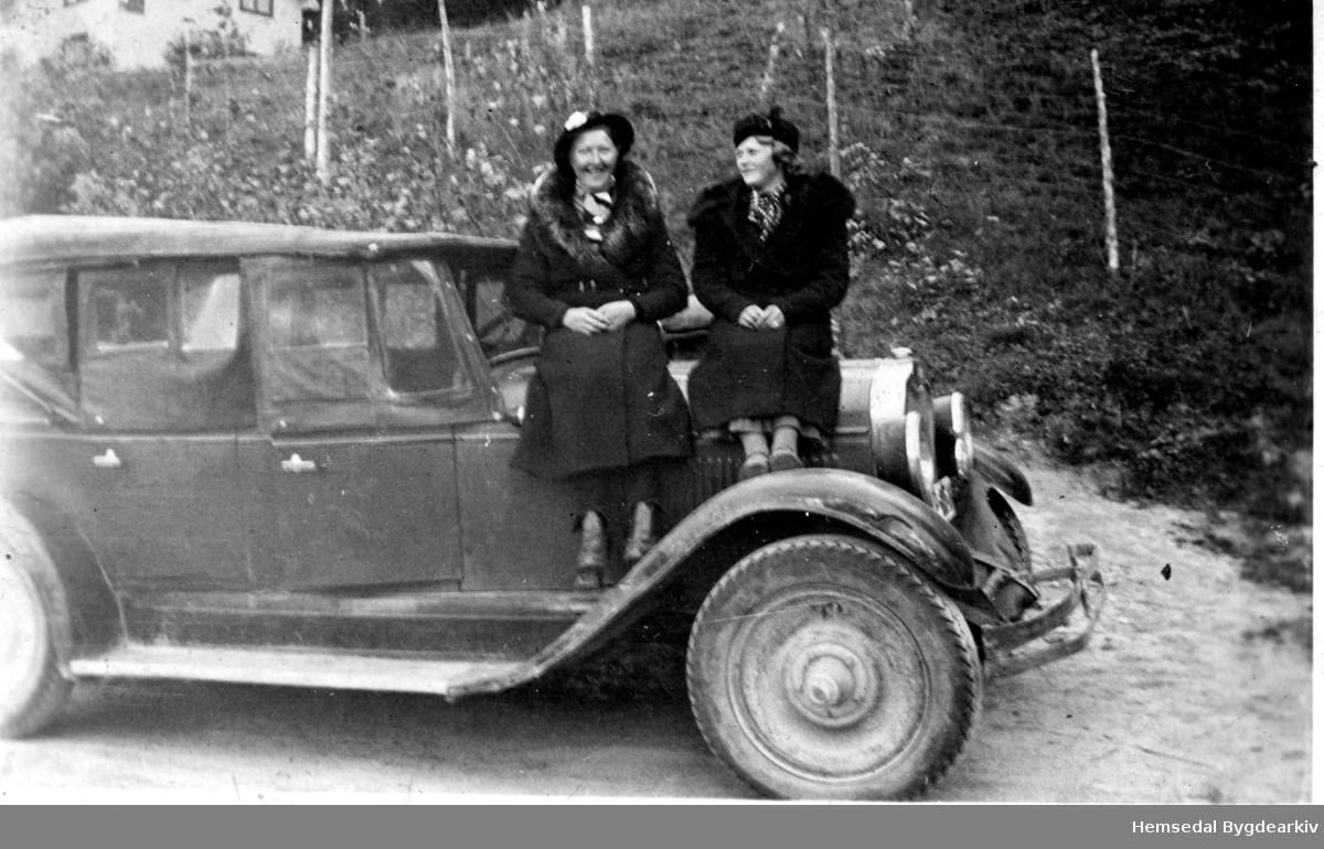 """Damene skal til byen og """"ta seg teneste"""". Frå venstre: Kari Eikrehagen, fødd 1915, gift Jondalen og Kari Hatten, fødd 1913, gift Gjærde. Bilen: """"Oakland Vipped"""" som tilhøyrde OLa Jondalen."""