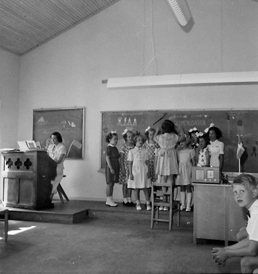 Rostaskolan, klassrumsinteriör, flickgrupp som sjunger, lärarinna vid pianot.Fröken Olsson
