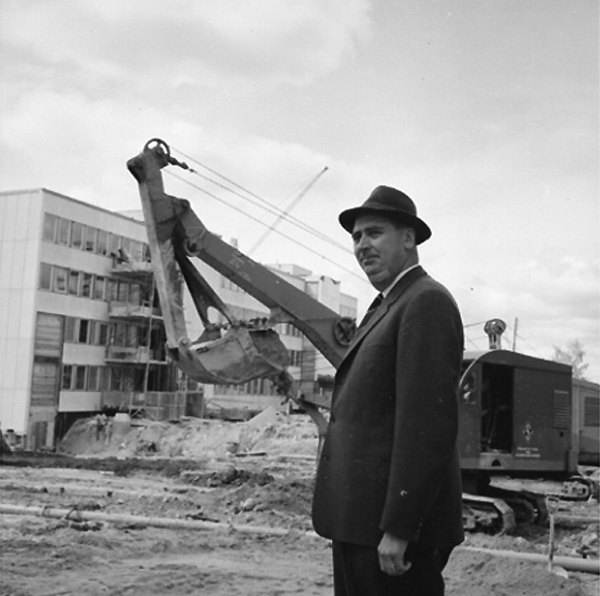 En man.  Byggnadsarbete i bakgrunden. Mannen på bilden är civilingenjör Karl-Elis Bowin som arbetade på AB Armerad Betong. Bygget av Stadsbyggnadshus 1 med adress Åbylundsgatan 8A Örebro.