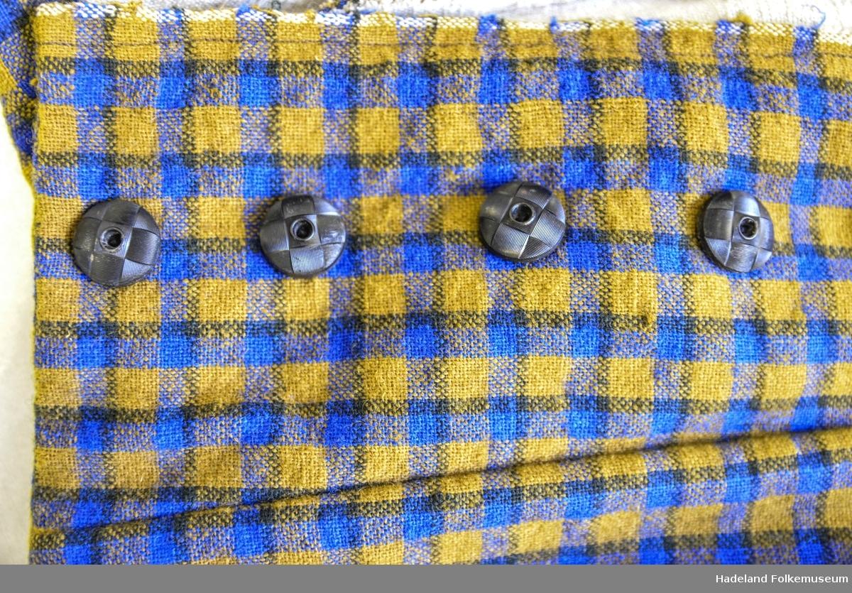 Kjole, kvinne. 2-delt heimeveved, helullsverken, lerretsbinding, rutet i blått, gulbrunt og svart. Jakke, lang innsvingt, foret med ubleket linstrie. Lange rette ermer med oppslag. Lukket med 14 svarte knapper + knapphull foran.  Skjørt: Bestående av 5 bredder utskrådd, folder i sidene. lette rynker bak. Skonnert med linstuet slitebånd i skjørtekanten.