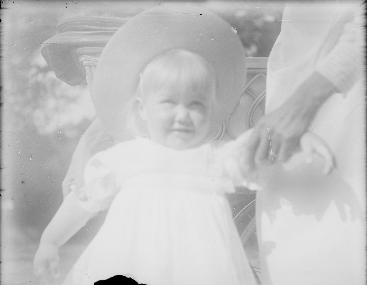 Barnet på bildet er Iacob Ihlen Mathiesen yngste sønn av Christian Pierre Mathiesen og Celina Ihlen Mathiesen. En kvinne som vi bare ser litt av holder barnet i armen. I bakgrunnen sees en barnevogn og lys mellom bladverket på trær.