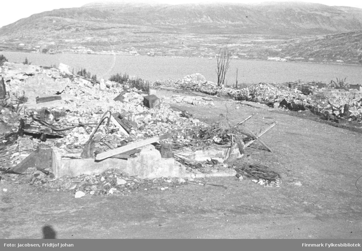 Ruiner i bydelen Haugen. Deler av en grunnmur med rester av murstein, betongbiter og forvridd jern. Noen delvis brente planker i og ved siden av ruinhaugen. En grusvei går nedover mot en annen vei som går på tvers. Rett nedenfor veien ligger en ruinhaug til. Et enslig tre står ved siden av denne ruinen, og en stor stein ligger på kanten av terrenget. Sjøen som ses litt oppe på bildet er innseilingen til Hammerfest. Øverst til høyre på bildet er foten av Fuglenesfjell og videre mot venstre på bildet er bydelen Fuglenes. Fjellet helt øverst på bildet er Storfjellet og Vardfjellet helt ti venstre. Mellom Storfjellet og Fuglenesfjellet ligger Fuglensdalen som går opp mot Reindalen. Sjøen ligger rolig, ingen snøflekker i fjellet og delvis solskinn så bildet er nok tatt på en, tross alt, værmessig fin sommerdag.