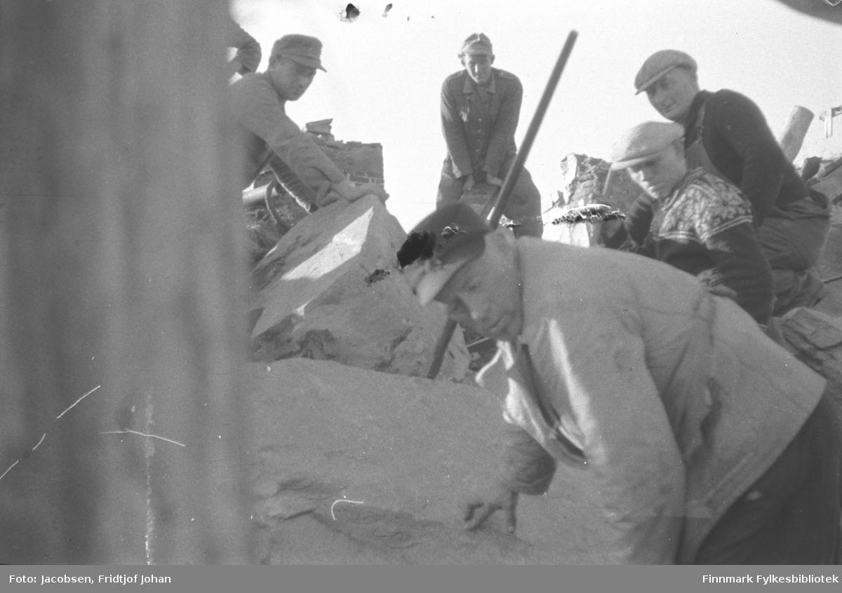 De to øverst på bildet er tyske krigsfanger som  deltok i oppryddingen i Hammerfest etter krigen. Ca. 400 krigsfanger var i Hammerfest og drev med opprydding og minesøk. Mannen helt foran i bildet het Hjalmar Josefsen. Alle fem mennene har skyggeluer på hodet og mye betong- og steinrester ses på bildet