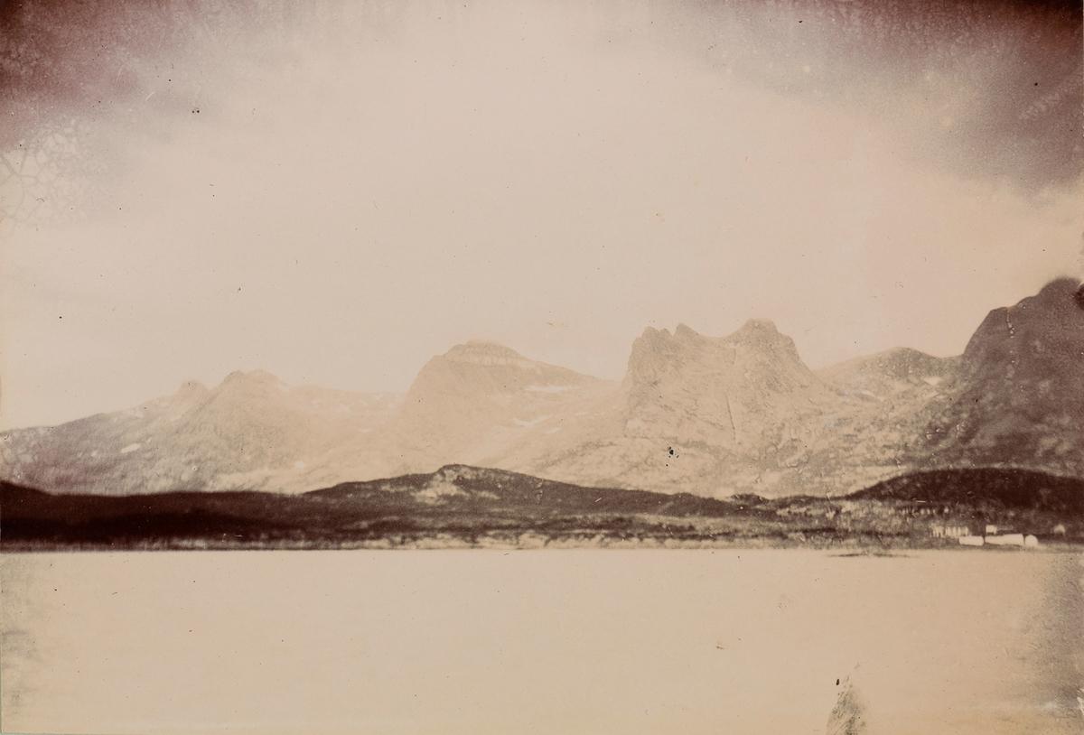 Fjord- og fjellandskap med seks av de syv søstre i bakgrunnen: Botnkrona (1 072 moh.), Grytfoten (1 019 moh.), Skjerdingen (1 037 moh.), Tvillingan (945 og 980 moh.), Kvasstinden (1 010 moh.) sett fra båten mellom Alsten og Herøy/ Dønna.