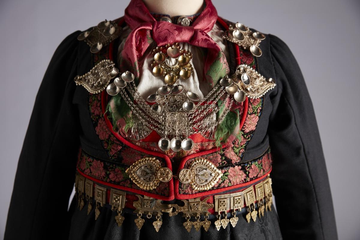 Svart stakk med silkefløyelsbånd med brosjert blomstermønster, kantet nederst med smal rød rouleaukant.