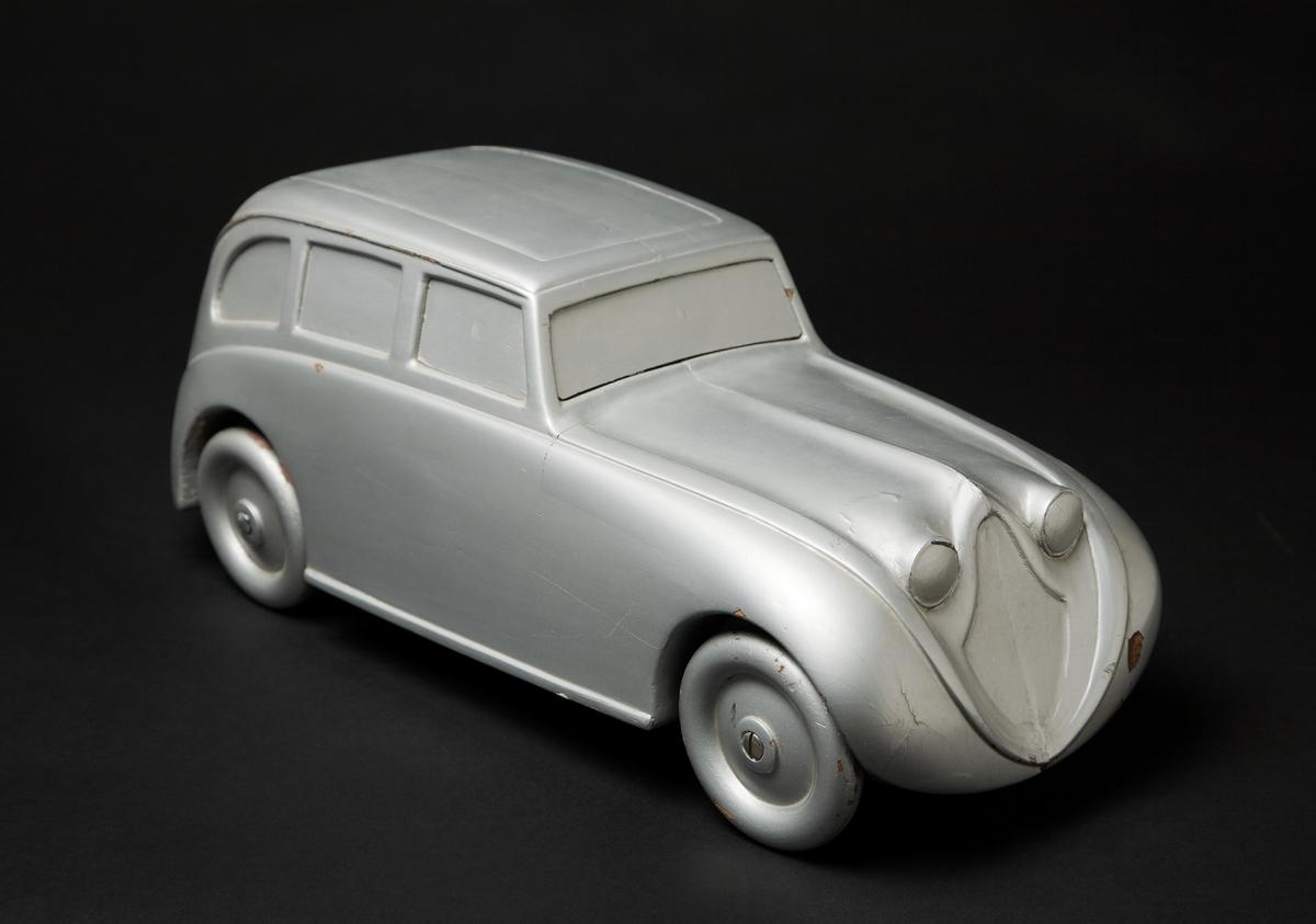 Trämodell i skala 1:10 som visar ett tänkt utförande av den bil som byggdes 1933. Skulpterad ur ett limmat träblock, med svarvade trähjul. Modellen omlackerad ett antal gånger för att prova olika färgsättningar.