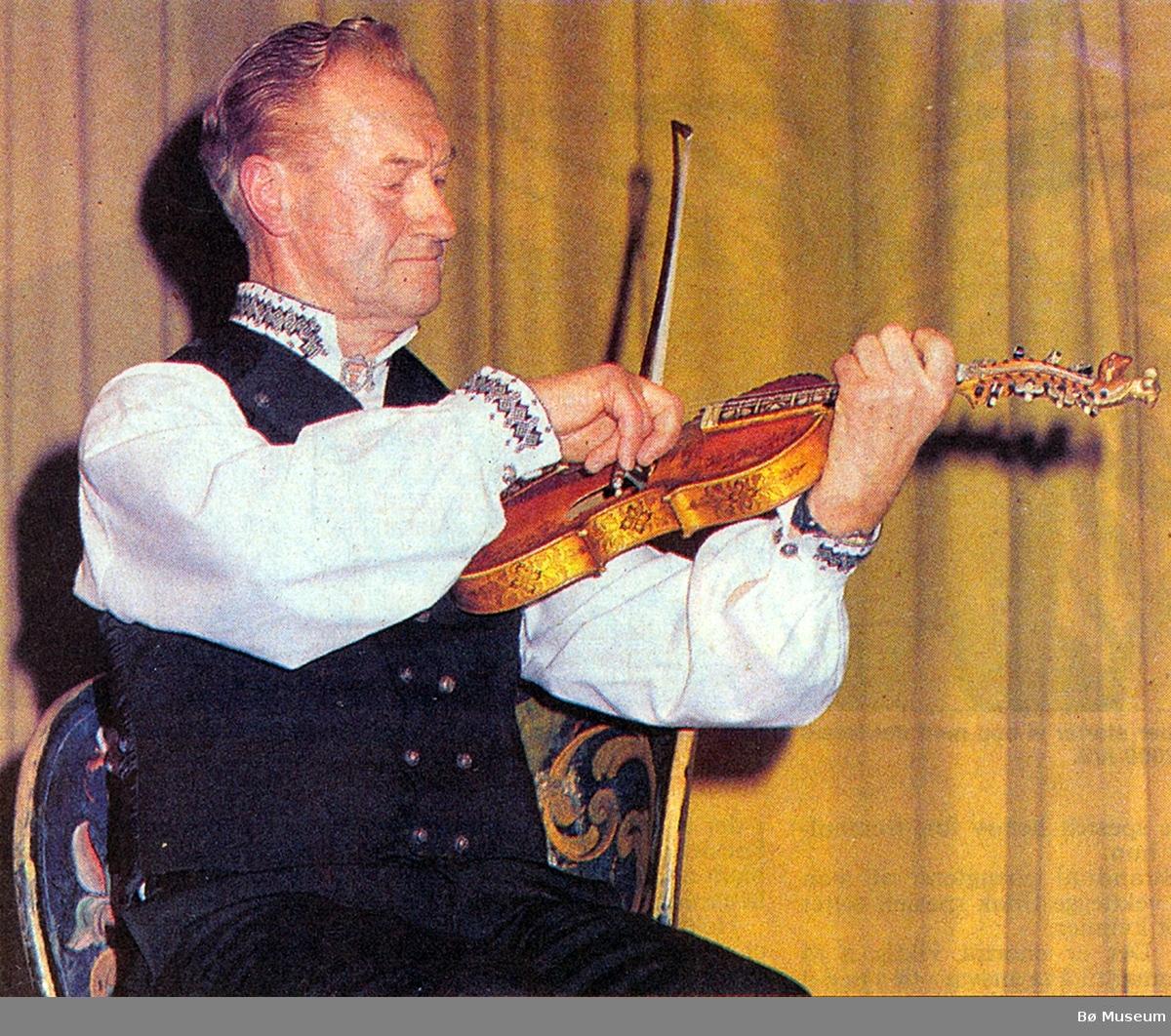 """Sveinung H. Dalen spelar """"Tjugedalaren"""" på minnekonserten for Jens Amundsen i 1991 på Sandvin. Sveinung spela mykje saman med Jens gjennom mange år. Her sit han på kubbestolen frå Borgja og spelar på Helland-fela """"Kjempa""""."""