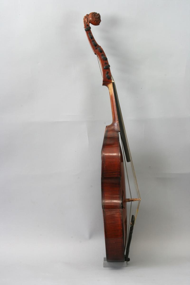 7 + 7 strenger. Instrumentet utvilsomt ekte, med noen få senere forandringer. Mørk brun lakk. Lokkanten av ibenholt, slangeformede lydhull med punkt. Skruene muligens orginale, men nå forsynt med tykke, innstemplede tall ved hodeenden.