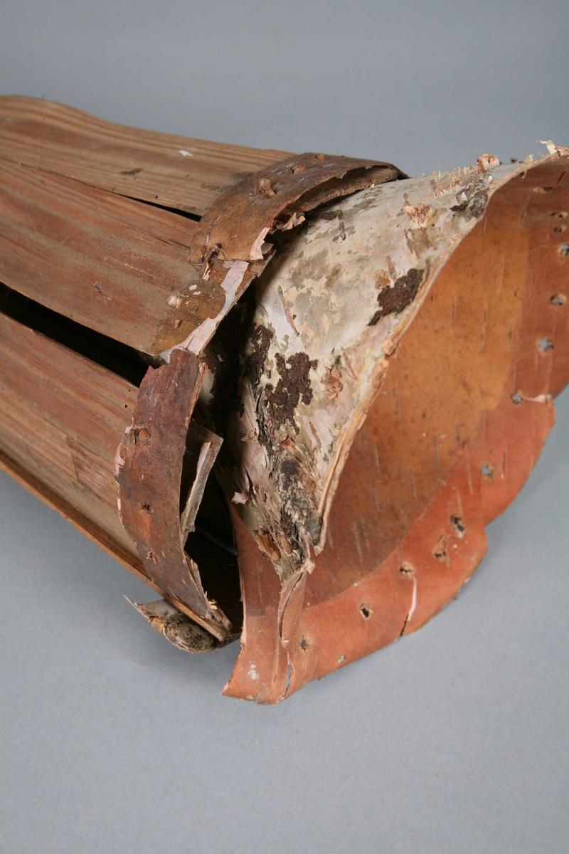 Modell av kileformet eller kjegleformet åleteine. Den er ganske smal. Det er et enkelt lag av bark rundt utsiden av åpningen og et tau på motsatt ende. På den ene siden er det et K-merke. Teinen har gått i oppløsning slik at trakten er løs.