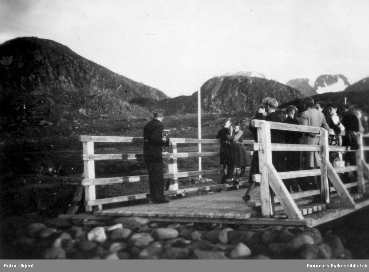 Dans på brua i Nuvsvåg 1944. Ungdommen fra Nuvsvåg danser med telegrafarbeidere fra Alta. Arbeiderne var der for å bygge opp den raserte telegraflinjen til Nuvsvåg. På bildet kan man se menn og kvinner i dans. Mennene har på seg bukser og jakker, kvinnene kjoler. Enkelte av kvinnene har på seg gensere. En mann spiller trekkspill helt til venstre. I bakgrunnen kan man se fjell og en flaggstang.