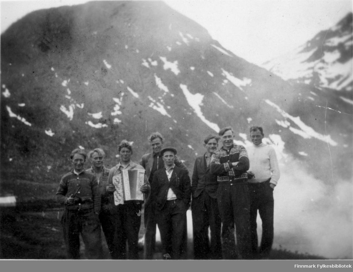 Telegrafarbeidere fra Alta sommeren 1944. De arbeidet med å strekke telefonlinje mellom Nuvsvåg og Gammelvær- Ulsfjord. Mennene er kledd i bukser, gensere og skjorter. Mannen som er nummer én fra venstre holder på en pipe og mannen ved siden av har et trekkspill i hendene. Mannen i midten av bilde har på seg en lue.