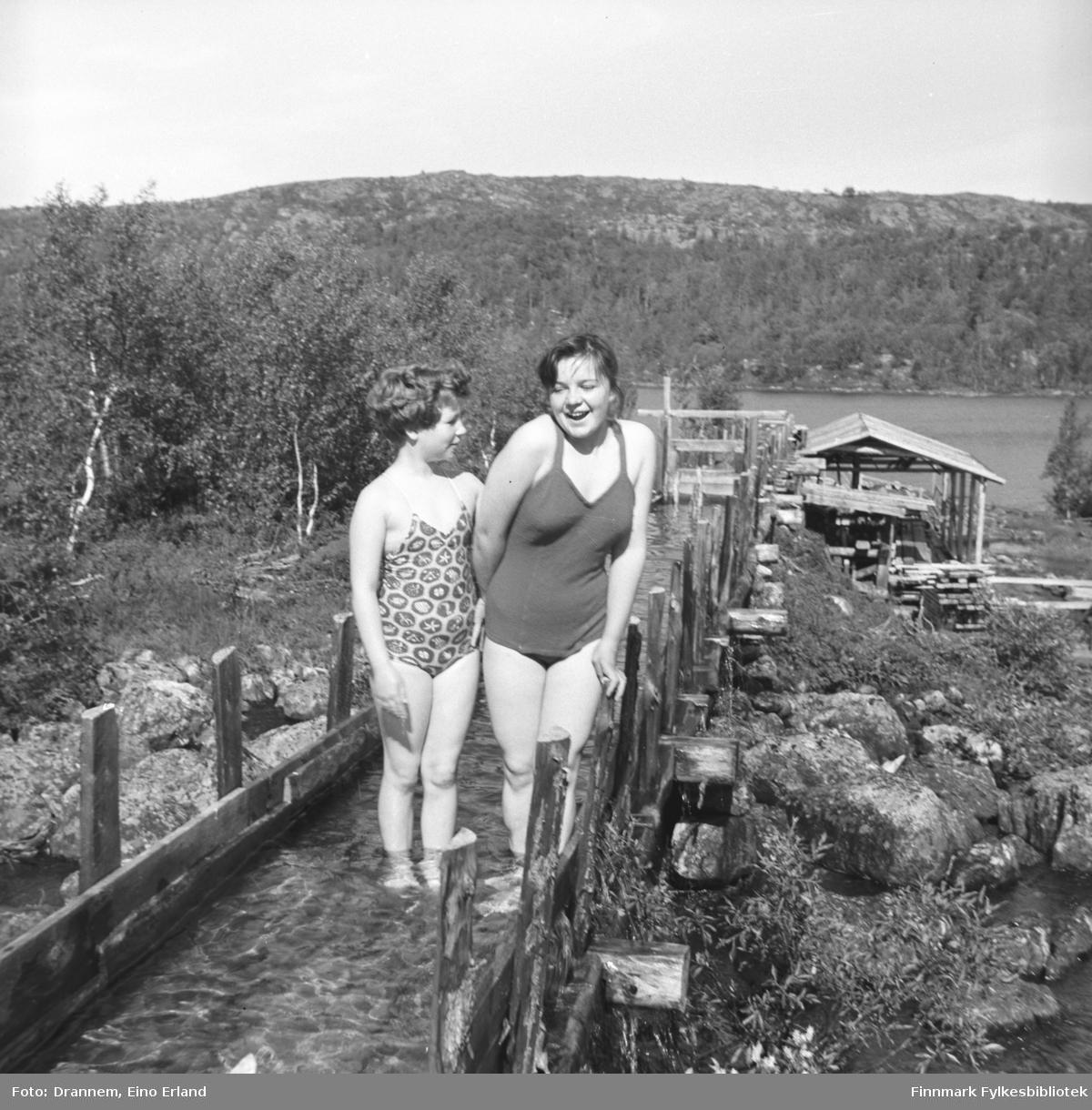 To jenter iført badedrakter,, Turid og Maija, står i en vannrenne som går til noe som ser ut som et lite sagbruk. Turid til venstre på bildet.