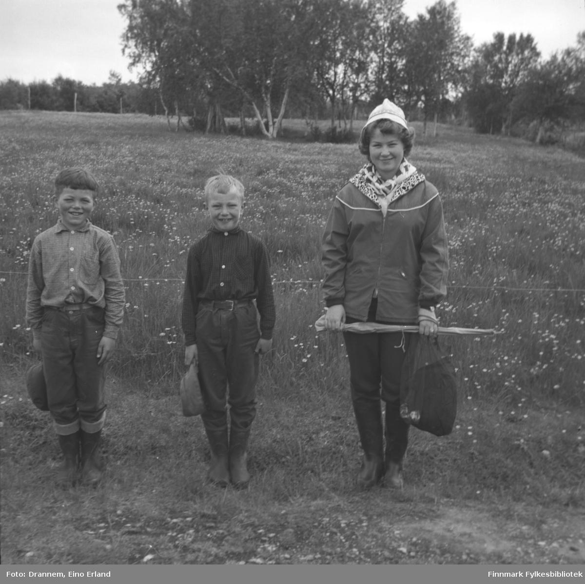 Tre barn fotografert på et jorde. Til venstre på bildet står Ingolf E. Eriksen,  i midten Ole Gabrielsen og til høyre står Turid Karikoski.