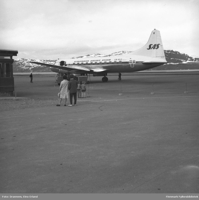 Turid Karikoski og Jenny Drannem, med et SAS-fly parkert foran stasjonsbygningen i Alta.
