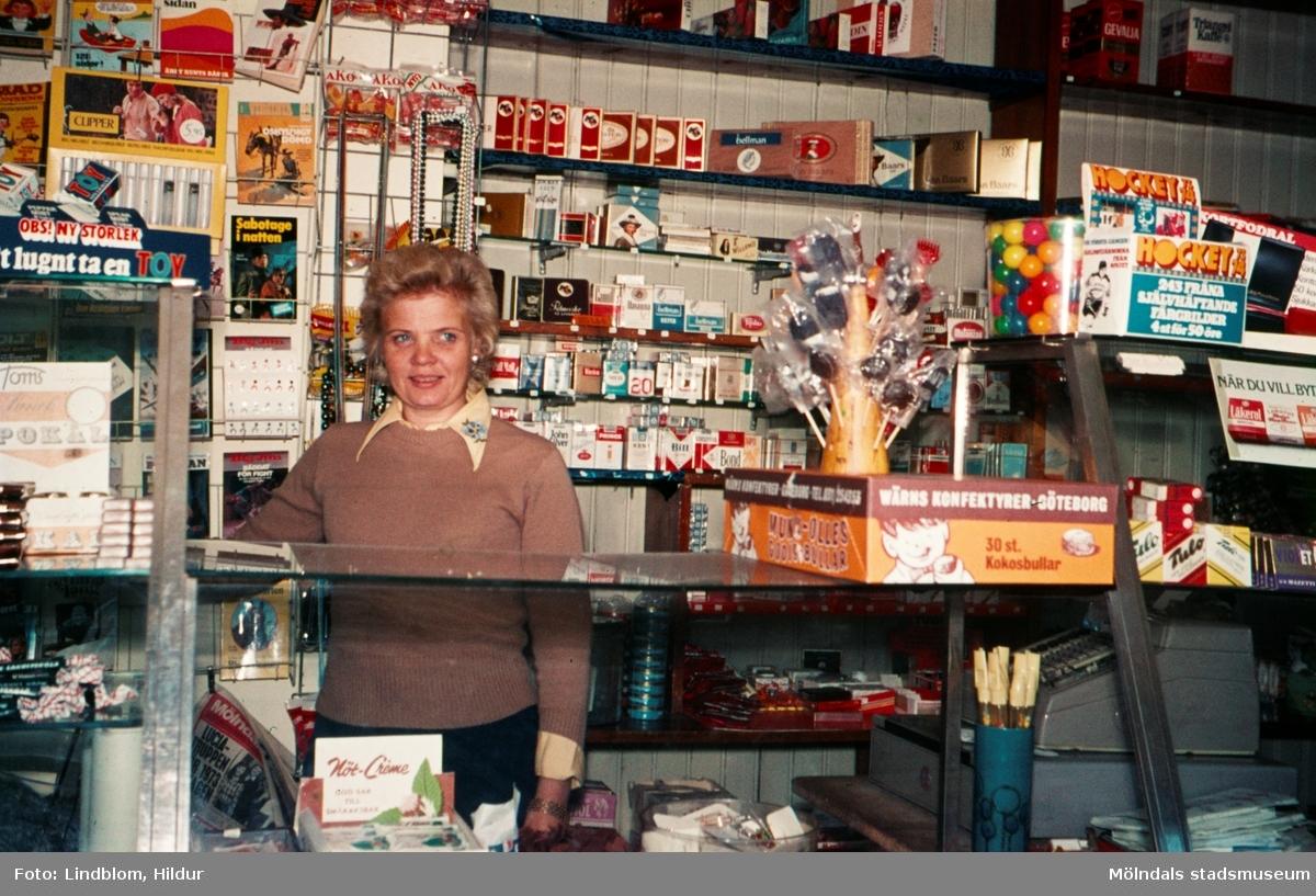 En kvinna bakom disken i en tobaksaffär, år 1973. Möjligen vid eller i närheten av Gamla Torget i Mölndal.  För mer information om bilden se under tilläggsinformation.