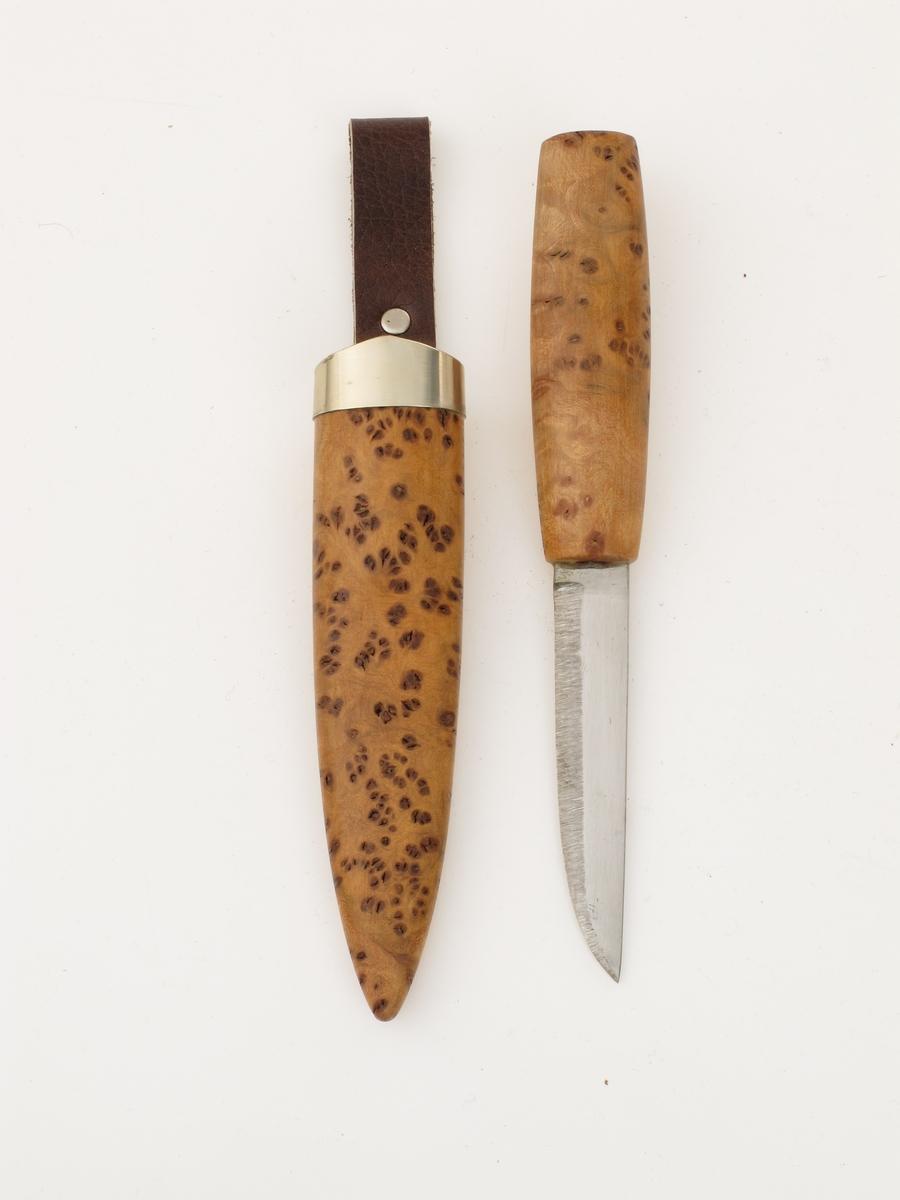 """Kniv, tilnærmet ubrukt. Stål blad. Skaft av rot-tre surna alm.  a) Kniv. Skaft ovalt tverrsnitt, veden lys og mørkere, marmorert med brune små prikker og """"hull"""" Bladet stemplet A.Ellefsen (noe grumset stempel). På samme side som stemplet er ujevnhet i stålet, liten rustflekk i spissen. Tilstand: ubrukt.  b)  Knivslire, Ovalt tverrsnitt, smalere i nedre 2/3. Sølvbeslag som går opp i spiss foran. Lærhempe mørkbrun med metallbeslag.  Lær, sølv  Treet har tett med små brune flekker, dels med små Hull. Innrisset bak:  MM.  Dobbel hempe."""
