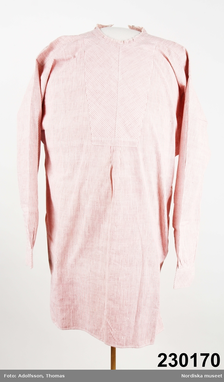 """Mansskjorta av fintrådig bomullslärft, smalrandig i rött och vitt.  Ett framstycke, 1 ryggstycke som är något rynkat  mitt bak mot axelok . Oket infodrat med vit bomullslärft. Sidsömmar med sprund.  Fram på bröstet ett påsytt """"skjortbröst"""" av samma tyg med ränderna lagda diagonalt, mitt fram ett litet knapphål för lös skjortknapp, 2 cm bred halsslå, för löskrage,  med knapphål mitt fram. Sprund i ryggen 25 cm med knappslå, knäppt uppe vid nacken med 2 små vitmetallknappar. Vidsydd ärm med ärmspjäll, nedtill rynkad mot enkel manschett  skuren på diagonalen , ärmsprund, knäppt med 1 knapp och knapphål .  I mycket fint skick. Fint lappad för hand med samma tyg på höger underärm.  /Berit Eldvik 2012-12-21"""