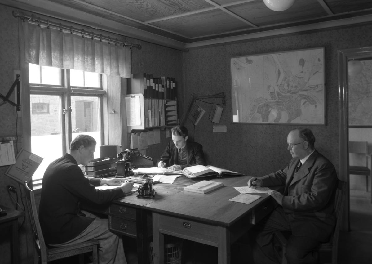 På kontoret hos AB Frans Elinder år 1943. Mannen till höger är förre kakelugnsmästaren von Knorring. Mannen i mitten är Jarl Wallin som jobbade som kamrer i många år på Elinders, som senare blev Beijer Byggmaterial.