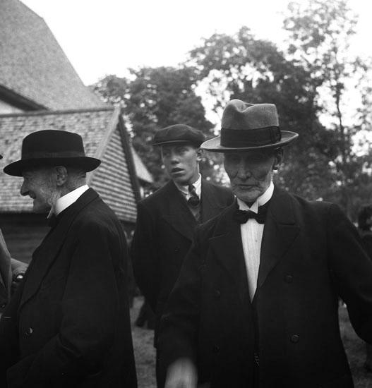 Foto av två äldre män och en ung man med mörka kostymer, som står vid Vederslövs kyrka.Christina Nilsson-jubileet 1943.