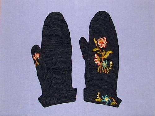 Ett par smygmaskvirkade tumvantar av svart ullgarn. Nervikt krage. Broderat blommotiv med kulörta färger i plattsöm på ovansidan, tummen och kragen. Längd med utvikt krage: 30 cm. Vantarna står inskrivna på äldre registreringskort från Gotlands Fornsal som krokad vante och är nu inskrivna som smygmaskvirkade.  Sökord: Ull.