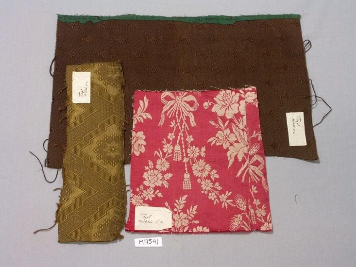 Tre stycken prover på möbeltyg, gulgrön, brun och röd.  Brun, Ripsbindning i botten med varp floteringar som           bildar mönster. Liljor och prickar. Storlek 510 x 320 mm.  Gulgrön, Vävt i rips och satin med mönster av 8-uddsstjärna med                en bård runt om. Storlek; 360 x 125 mm.  Röd, röd/vit damast med mönster av blommor och blad samt rosett           med nedhängande tofs. Storlek; 270 x 290 mm.  Alla tre proven har fastsydda papperslappar med texten; Tagel, Mistelås socken.  Inskrivet i huvudbok 1935.