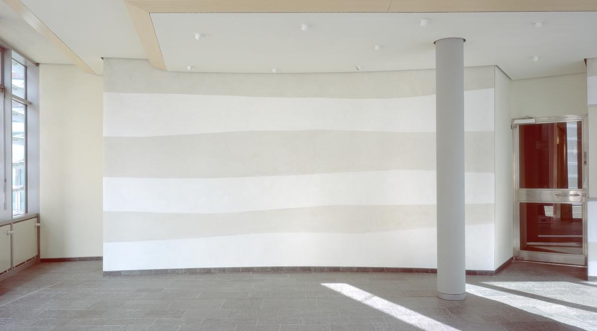 Verket tar opp og fører videre en tematikk som arkitekten har berørt, og som kommer til uttrykk i den store flate monolitten av norsk granitt som danner frontsiden av bygningen. Fremsiden av denne har en glattslipt, bølgete overflate som har blitt formet av isskuringen i østfoldområdet under istiden. De avvekslende horisontale linjene i veggbildet, som dannes av skiftningene i materialet, henspiller på de sedimentære avleiringene i Berlinområdet. Samtidig tar de opp de svungne linjene i monolittens profilsnitt hvor nedslipningen fra breisen er synlig. Gjennom motsetningen mellom de horisontale bevegelsene i det sandgrå veggfeltet på den ene siden og de vertikale linjene til den solide steinblokken på den andre - og gjennom forbindelsen mellom dem - ligger det et utsagn om vide rom og tidens forløp. Substansen i materialet inngår stadig nye forbindelser med lyset. I det vekslende spillet av dagslys og kunstlys oppviser veggen stadig nye kvaliteter.