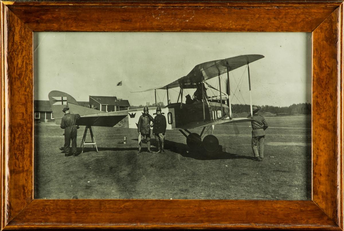 Flygplan Albatros NAB 9 nummer 760 ur Flygkompaniet står på bock på flygfält på Malmen. Två flygare poserar framför flygplanet. En flygare sitter i förarsitsen. Vid flygplansstjärten arbetare en tekniker med flygplanet. Inramat fotografi med träram.