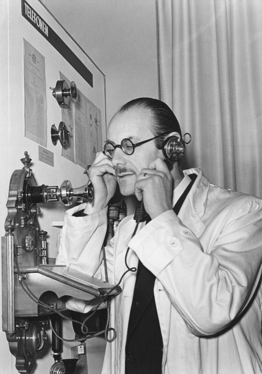 Museidirektör Torsten Althin demonstrerar en av L.M. Ericssons första väggtelefonapparater vid öppnandet av utställningen Idé- Patent- Produkt, på Tekniska museet den 6 december 1941.
