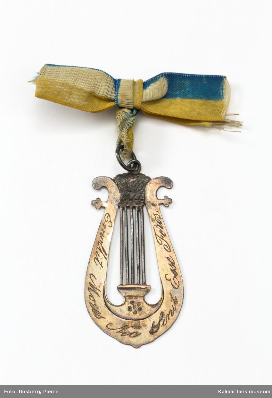 KLM 28256, Medlemstecken, av metall och tyg. Medlemsmärke i form av en musiklyra med en blågul rosett. På lyrans ena sida är texten Emollit Mores Neo Sinit Esse Foros präglat och på den andra d:6 Novemb: 1815. På märket hänger en pappremsa med en text: Medlemstecken i Kalmar musiksällskap, har tillhört fru Ebba Baerendtz. Gåva av kanslisekr. E. Baerendtz, Stockholm.