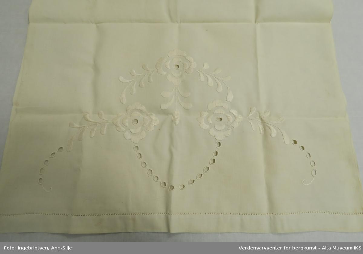 Stort pyntehåndkle med broderi i hver ende. Det ene broderiet er større enn det andre. Det store broderiet er av blomster og blader, mens det minste ser ut til å være et monogram eller lignende.