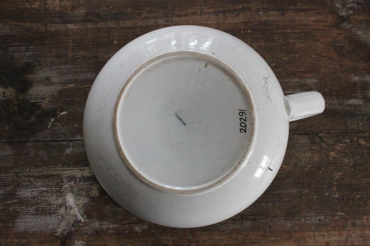 Rund potta med bukig vägg och platt 23 mm brett bräm. S-svängd lodgrepe. Vitglaserad. Under botten stämplat i godset: A2, B samt oläslig stämpel.