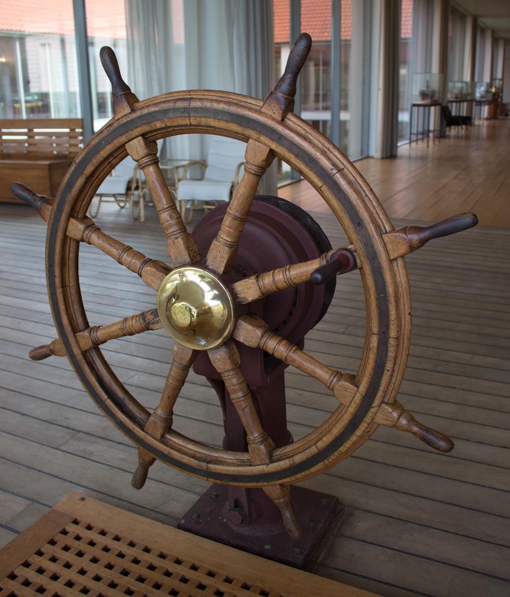 Skipsratt i teak eller eik med utveksling. Navet er messingbeslått, metallhåndtaker er malt brunrød.