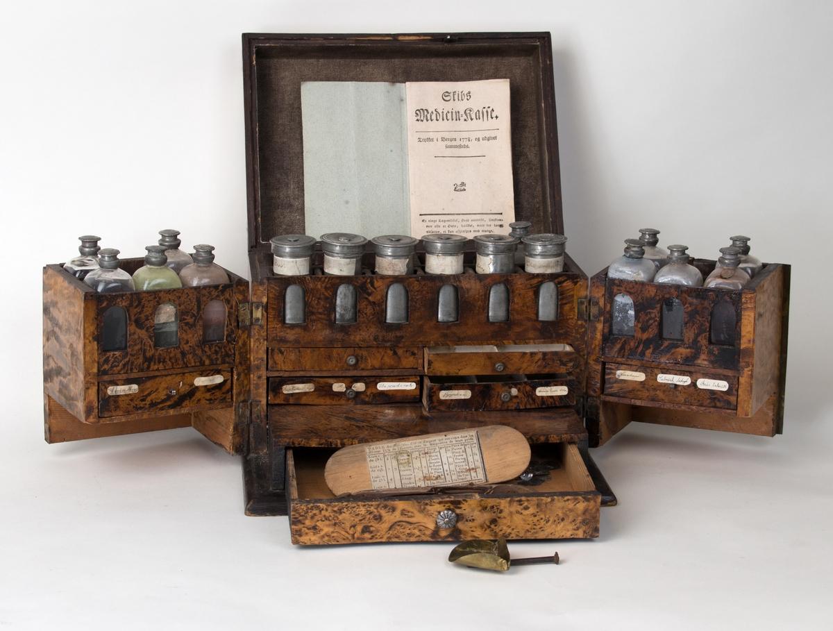 Medisinskrin i mahogny med diverse små skuffer, flakser og beholdere samt instruksjonsbok og skålvekt for måling av medisiner.