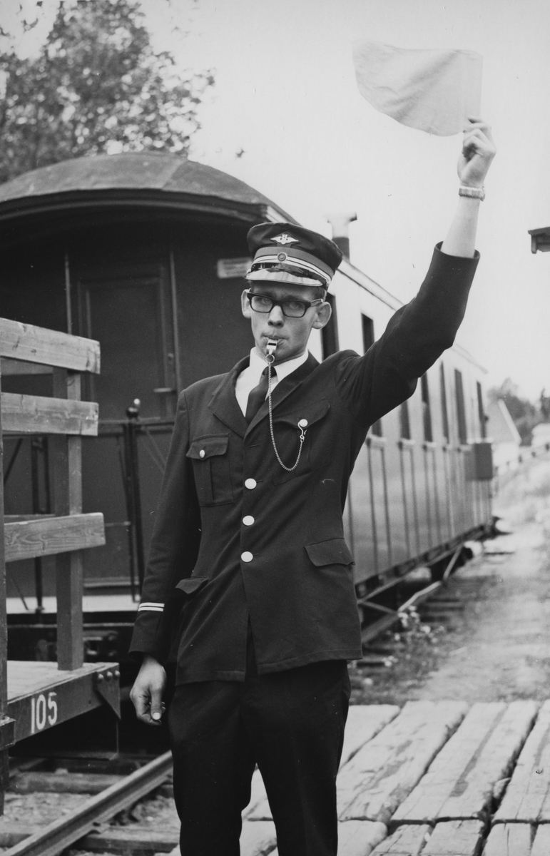 Togføreren gir avgangssignal for tog på museumsbanen Urskog-Hølandsbanen