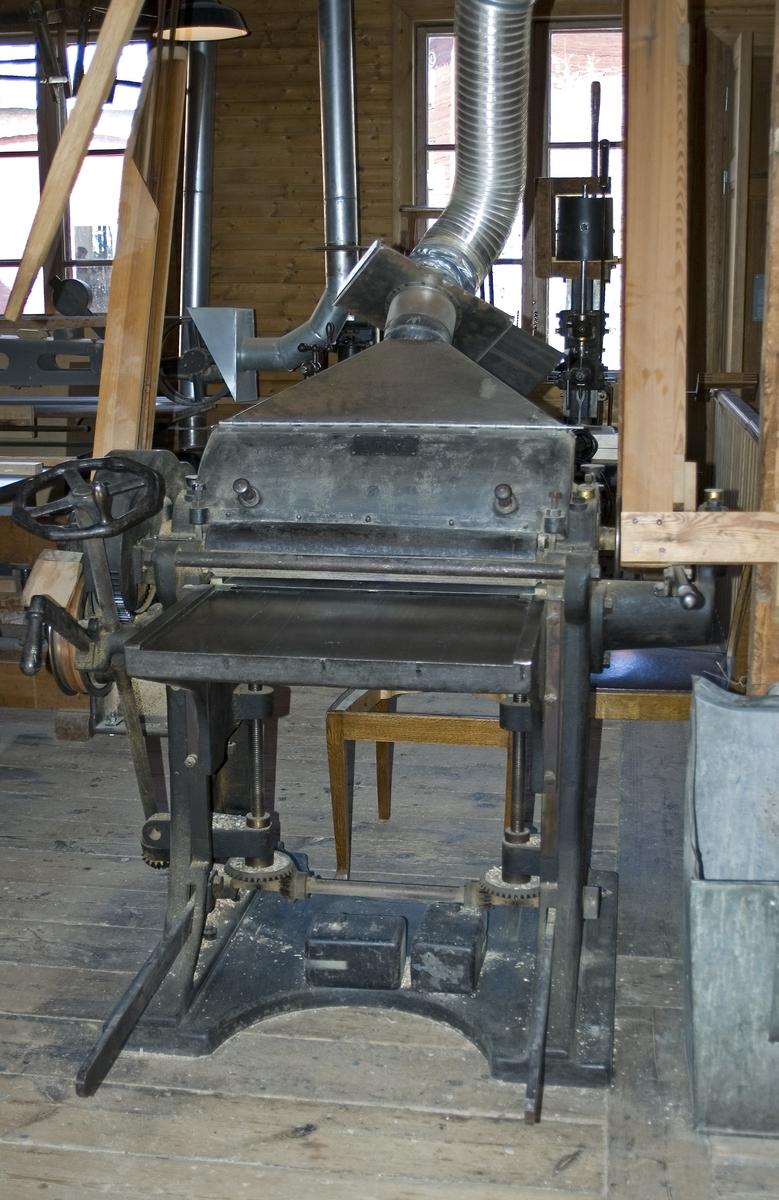 Hyvel med helgjutet stativ av järn. Planhyveln är avsedd för att hyvla ut tjockleken på träet. Hyveln drivs med remdrift från transmission i taket.  Funktion: Maskin för hyvling av trä