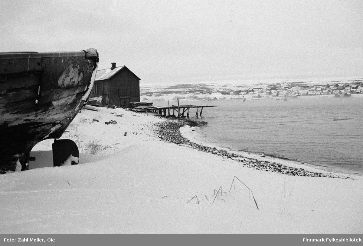 Vadsø 1968-69. Dette vinterbildet er tatt ute på Vadsøya fra området ved Sildoljefabrikken/Vadsø Havn. I venstre forkant ser vi skroget på en båt som ligger på land. I bakgrunnen et gammelt kaianlegg med en kai som ser ut til å gå i oppløsning. I bakgrunnen sees Vadsøs bebyggelse. Det er skodde eller sterk vind på fjorden.