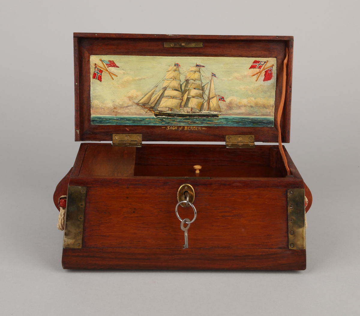 Modell av skipskiste med beslag, klamper og stropper. Seilskute bark SAGA malt i olje på innsiden av kistelokk. Leddik innvendig, samt lås med nøkkel.
