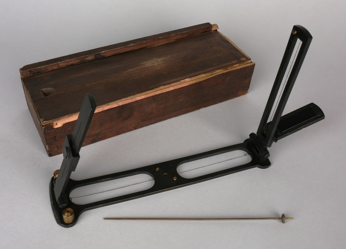 Peileapparat med siktedioptere og løs skyggepinn, ligger i liten trekasse med løst lokk.
