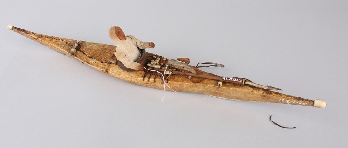 Kajakkmodell, med figur og fangstredskap ombord.
