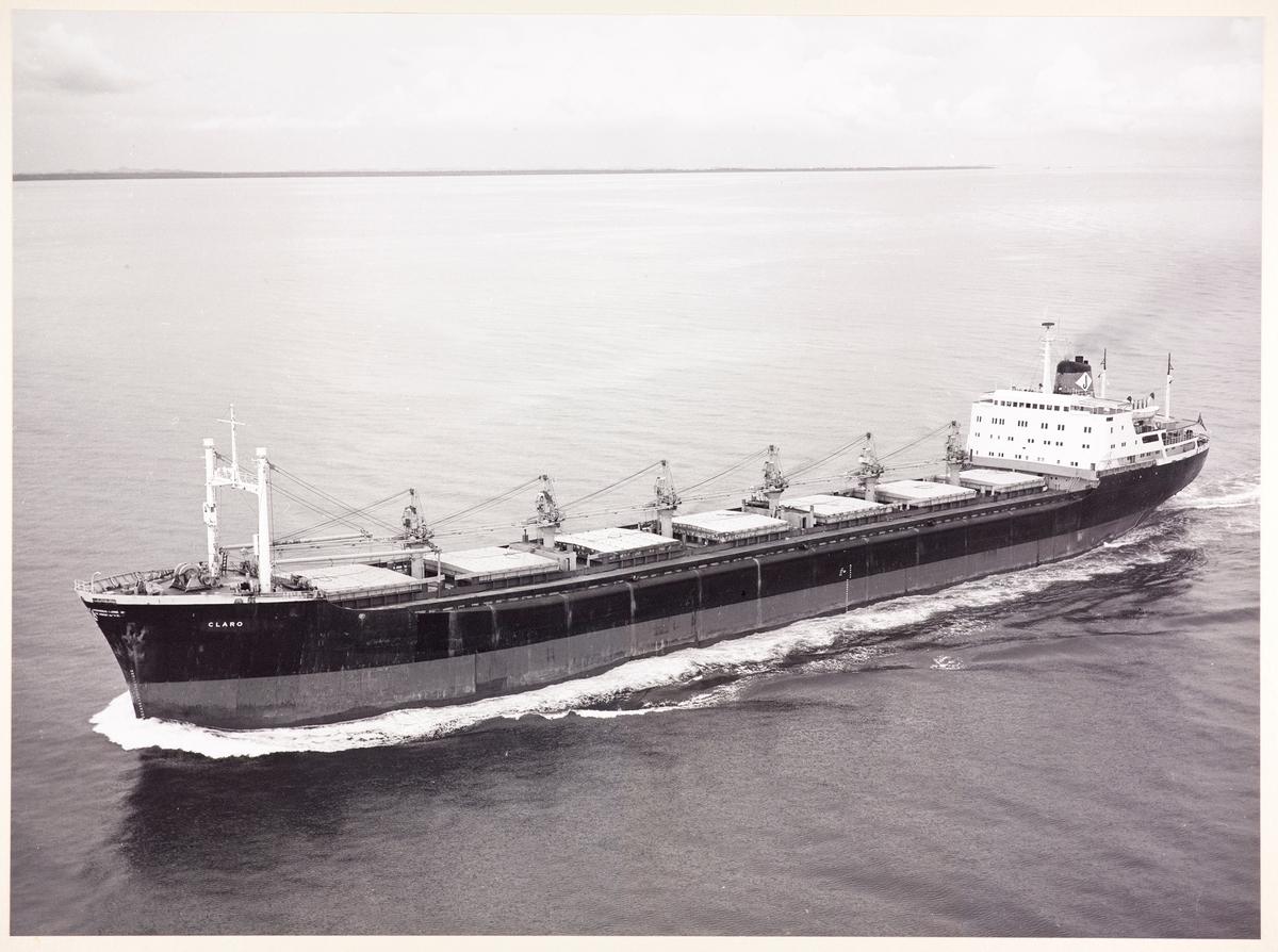 Flyfoto i sort-hvitt, av bulkskipet M/S Claro, tilhørende Jensens rederi i Arendal. Skipet beveger seg mot venstre i bildet. Landsktripe i horisonten.