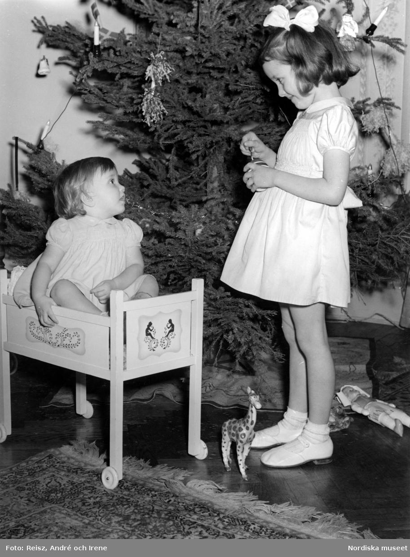 Två flickor vid julgran. Den yngre sitter i en docksäng på hjul