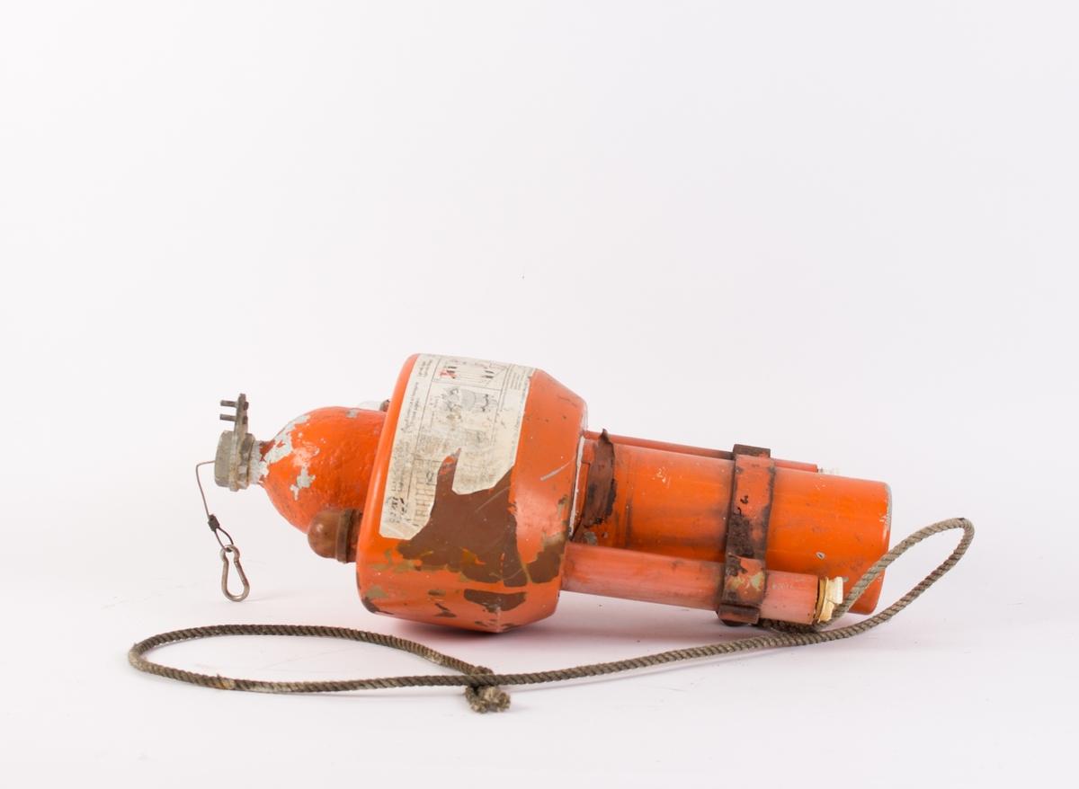 Nødsender til bruk på sjøen. Monteres sammen med livbøye og sender ut lys og røyksignal når den utløses. Gassbeholder i midten med to lys montert på hver side. Vaier med karabinkrok montert på topp av beholder samt del av tau festet til sokkel på sender.