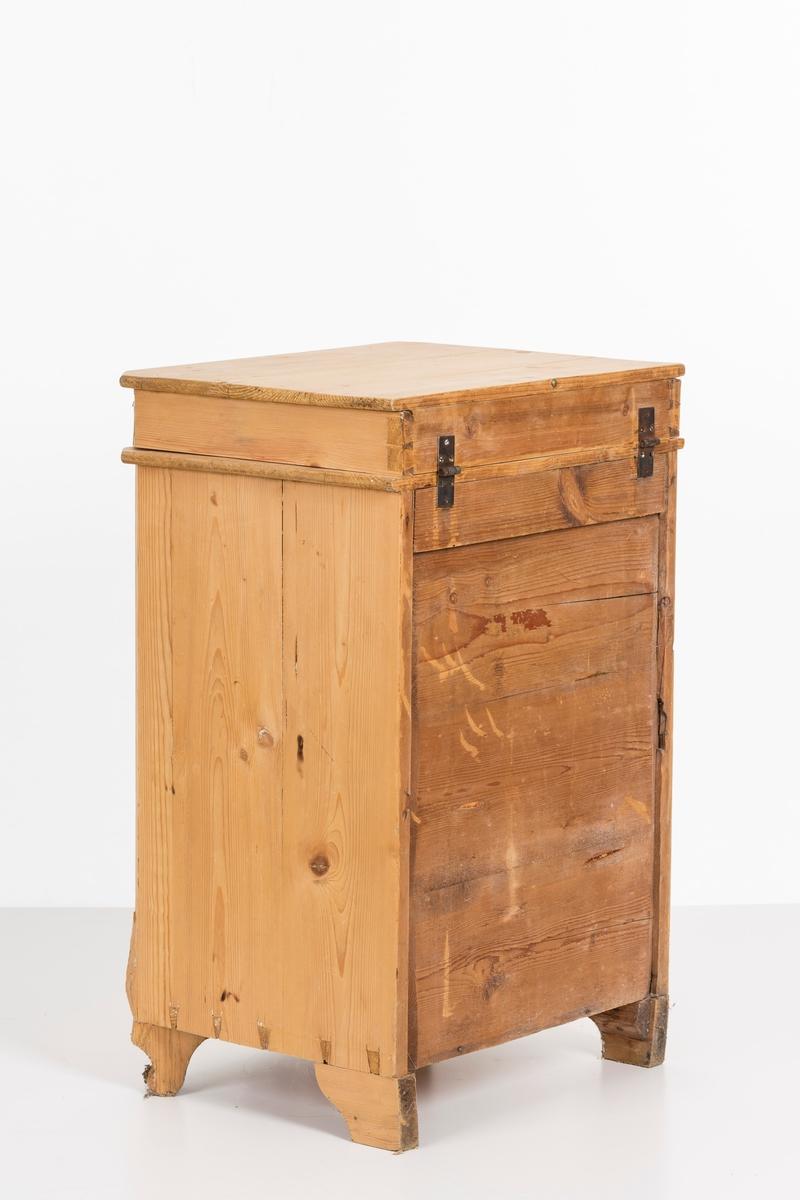 Toalettbord i ubehandlet tre. Det er rom for vaskebolle og skap under. Messingknott på døra til åpning og lukking, spor på innersiden av skapet kan tyde på at det tidligere også har vært en lås.