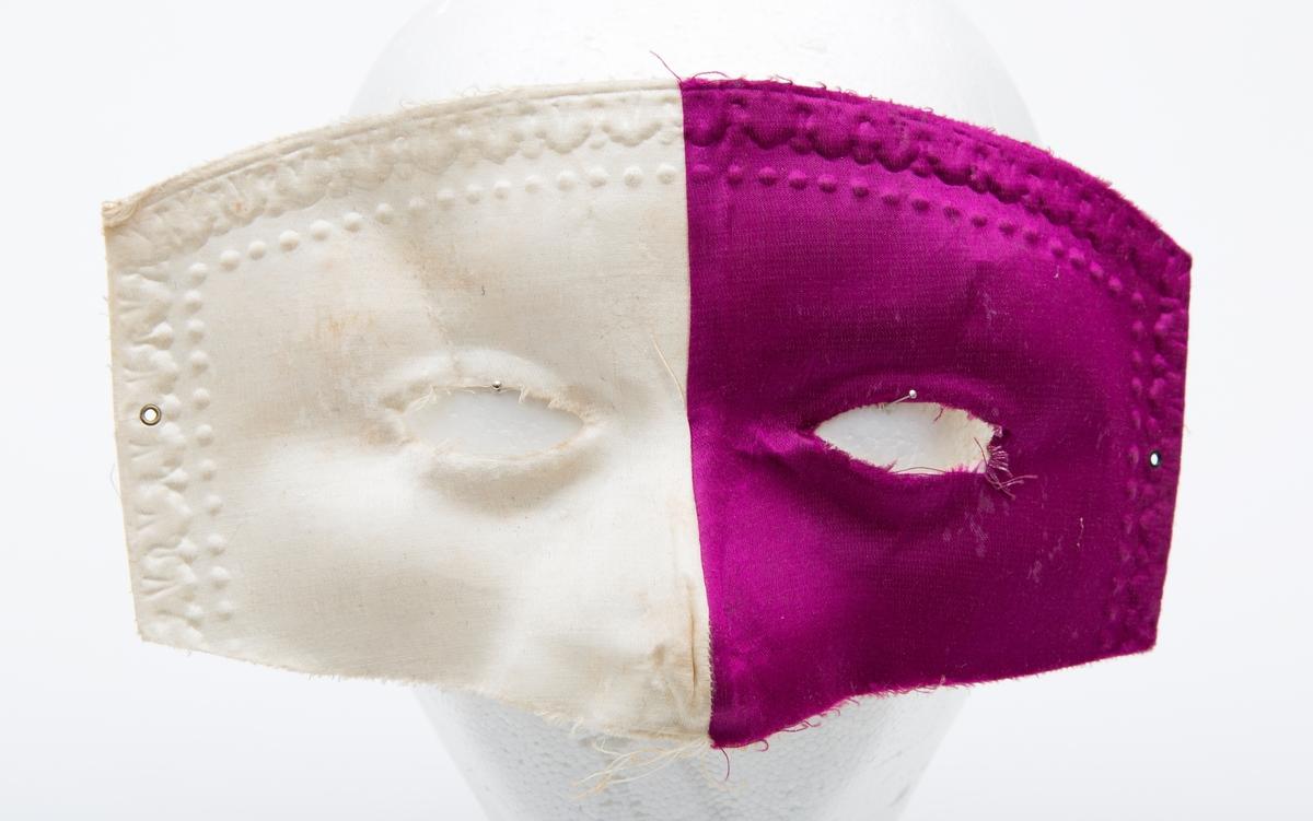 Karnevalsmaske, høyre halvdel hvit, venstre halvdel fiolett. Festesnor mangler.