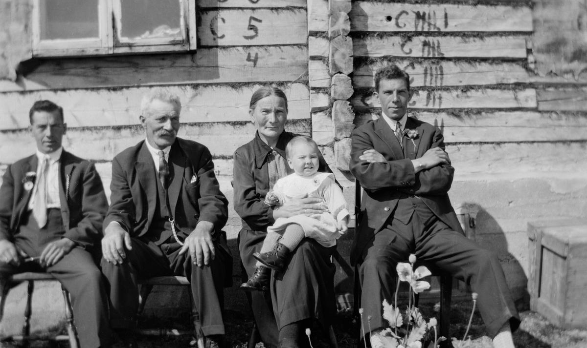 Tre menn, en kvinne og et barn foran nybygget hus.