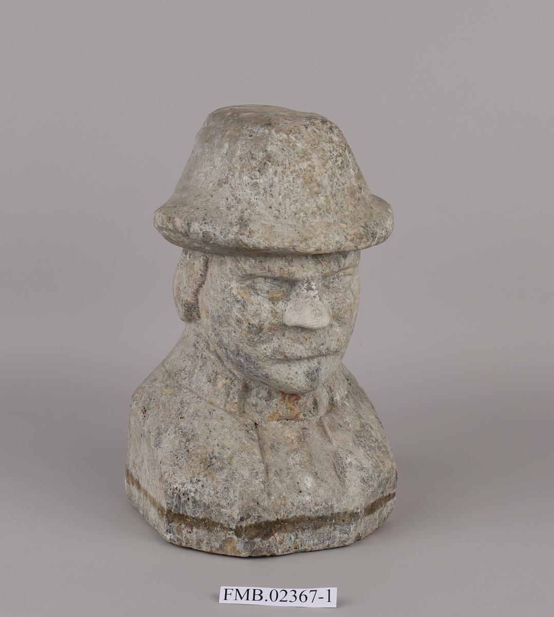 Hode og overkropp til mannsperson med hatt på hodet. Skal forestille Petter Dass.